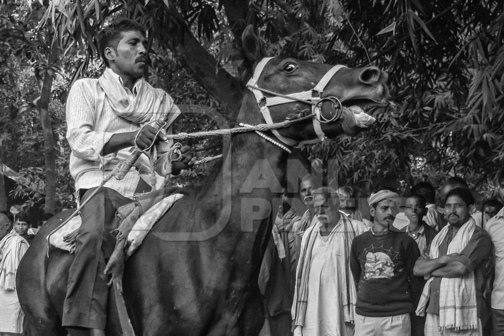 Horse in a horse race at Sonepur cattle fair with spectators watching in black and white